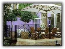 Islington job – raised terrace with 2 painted purple walls, white umbrella and patio heater